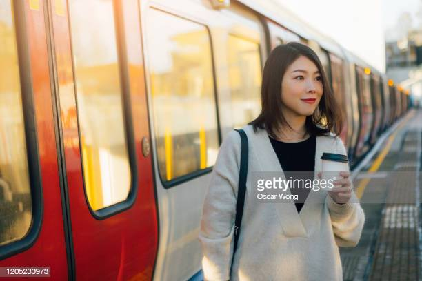 young woman using smart phone while alighting train - commuter stock pictures, royalty-free photos & images
