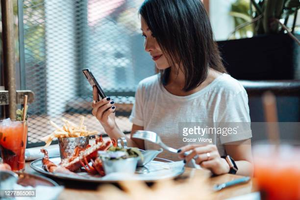 young woman using smart phone while eating at seafood restaurant - gourmet stock pictures, royalty-free photos & images
