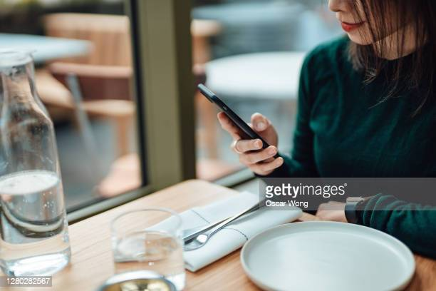 young woman using smart phone while relaxing at a restaurant - customer stock pictures, royalty-free photos & images