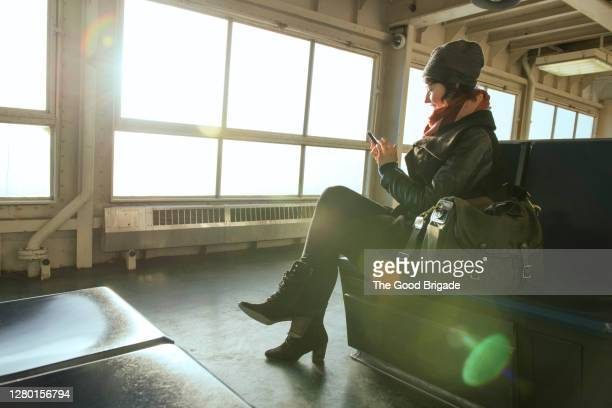 young woman using smart phone while riding on staten island ferry - ferry stock pictures, royalty-free photos & images