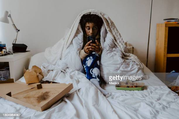 young woman using smart phone while sitting in bedroom - anxiety stock pictures, royalty-free photos & images