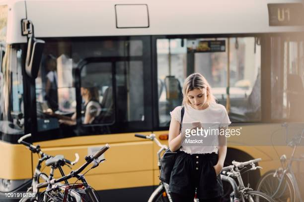 young woman using smart phone while standing by bicycles against bus in city - bus stock-fotos und bilder