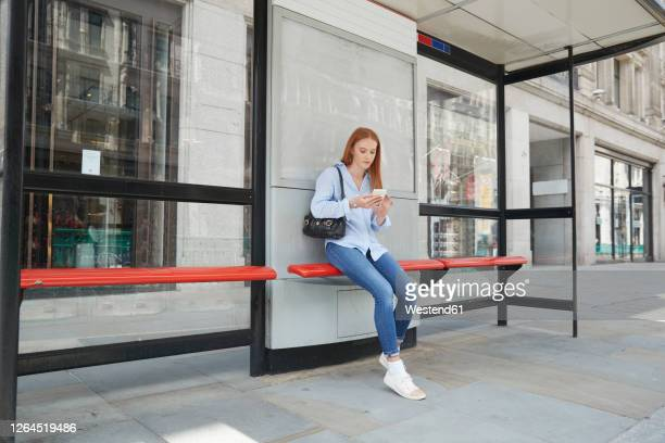 young woman using smart phone while waiting at bus stop in city - waiting stock pictures, royalty-free photos & images