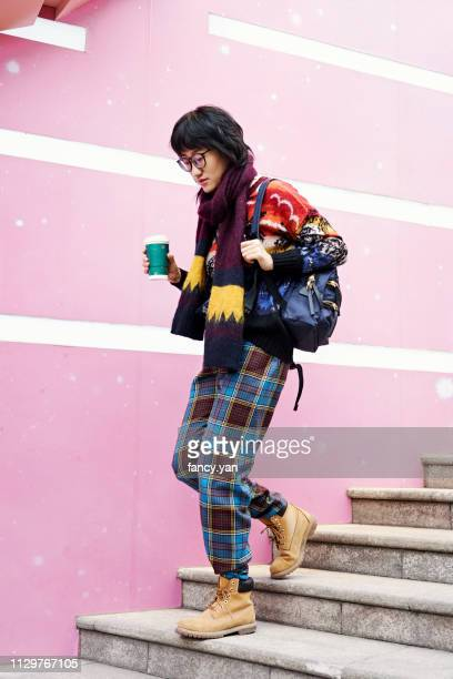 young woman using smart phone while walking down stairs