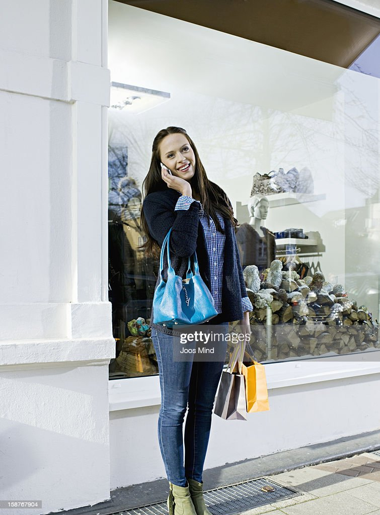 young woman using smart phone, window shopping : Bildbanksbilder