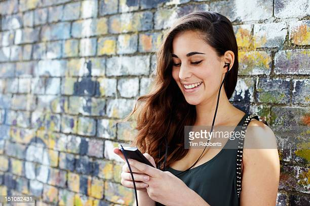 Young woman using smart phone with headphones.