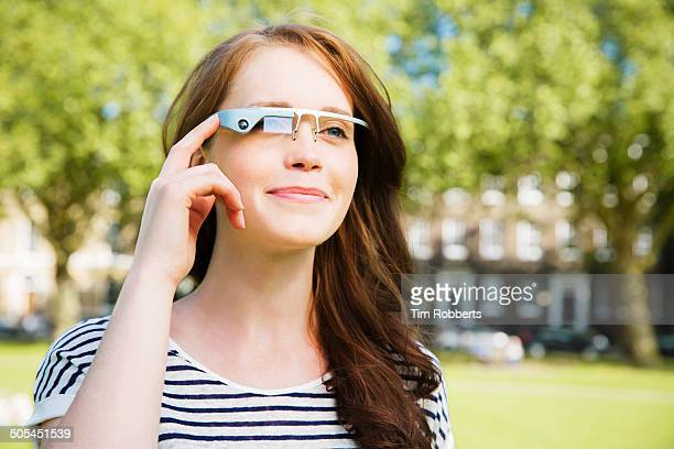 Young woman using Smart-Glass in urban park.