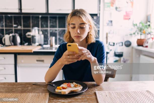 young woman using smartphone at breakfast - only young women stock pictures, royalty-free photos & images
