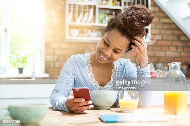 young woman using smartphone at breakfast - up do stock pictures, royalty-free photos & images