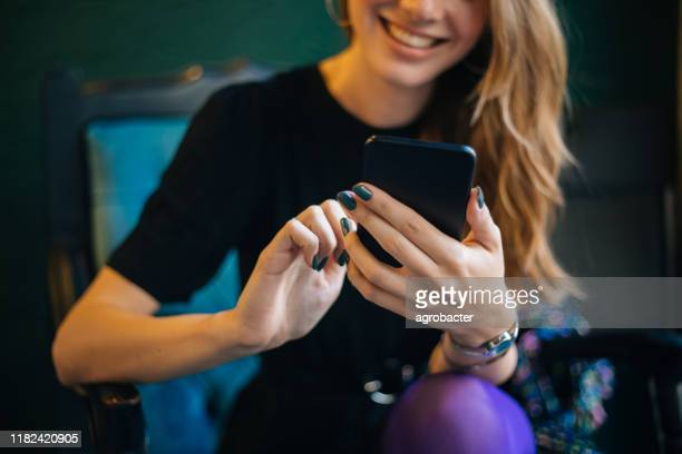 young woman using smartphone at cafe - phone message stock pictures, royalty-free photos & images