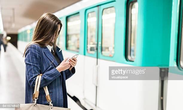 Junge Frau, mit Smartphone, bevor Sie in die U-Bahn
