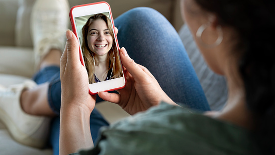 Young woman using smartphone for video call 1163987892