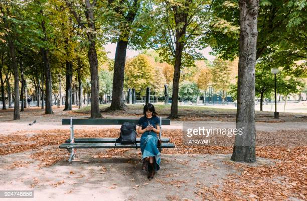 young woman using smartphone in a park - holy city park stock pictures, royalty-free photos & images