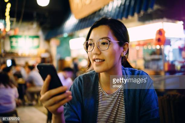 young woman using smartphone in a traditional style restaurant - customer stock pictures, royalty-free photos & images