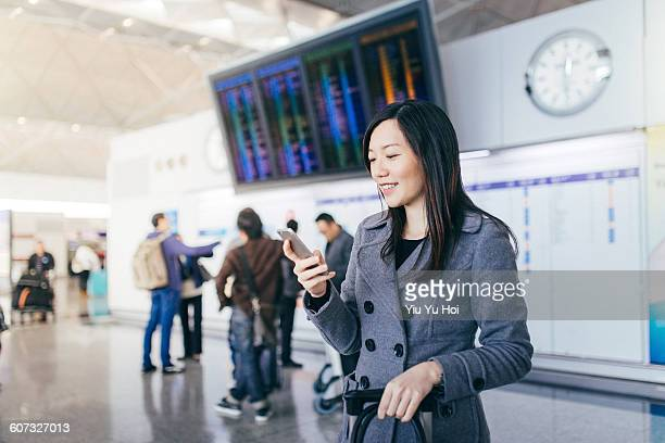 Young woman using smartphone in airport concourse