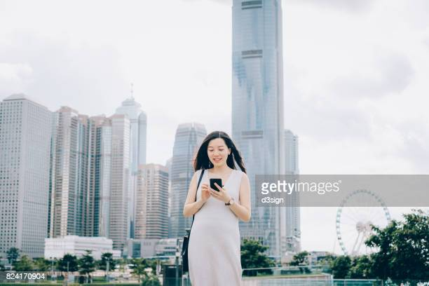 Young woman using smartphone in city against urban skyscrapers