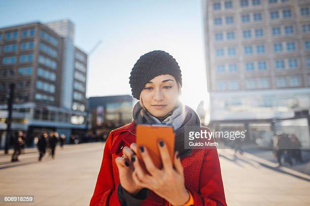 Young woman using smartphone in city.