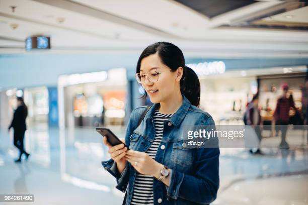 young woman using smartphone in shopping mall - consumerism stock pictures, royalty-free photos & images