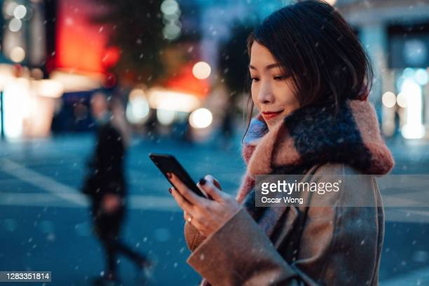 young woman using smartphone in the city at night - japanese ethnicity stock pictures, royalty-free photos & images
