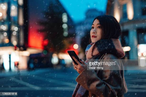 young woman using smartphone in the city at night - looking away stock pictures, royalty-free photos & images