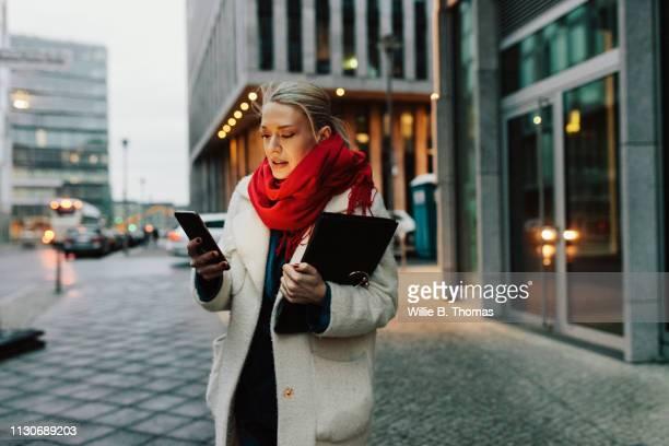 young woman using smartphone in the street - pañuelo rojo fotografías e imágenes de stock
