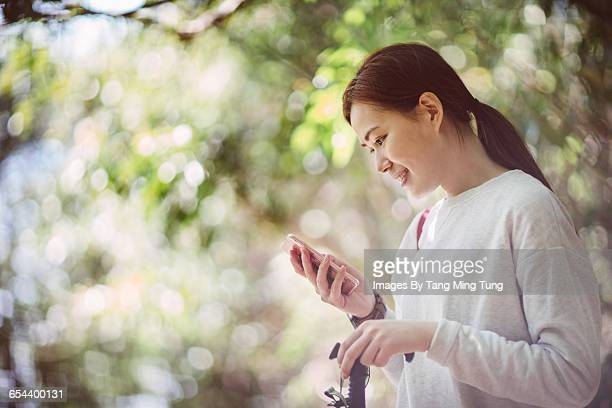 Young woman using smartphone joyfully