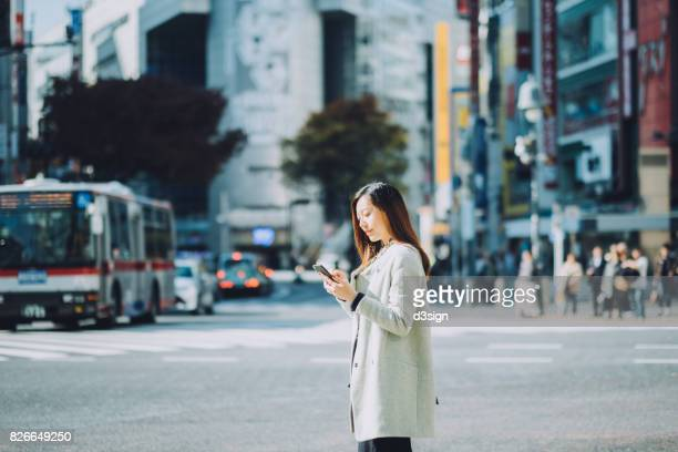 Young woman using smartphone on city street while waiting for taxi, against busy transportation and commuters