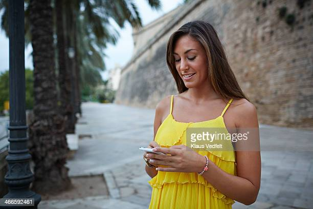 young woman using smartphone on old street - klaus vedfelt mallorca stock pictures, royalty-free photos & images