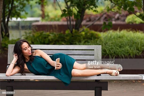 Young woman using smartphone on park bench