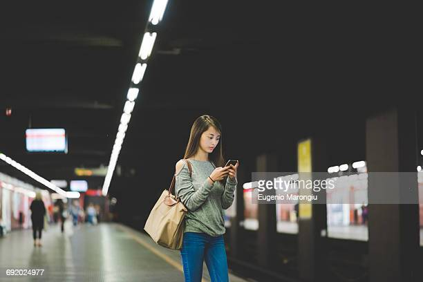 young woman using smartphone on railway platform at night - railway station stock pictures, royalty-free photos & images