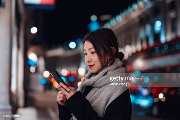young woman using smartphone on the city street at night - waiting ストックフォトと画像