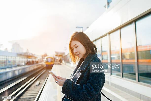 Young woman using smartphone on the train platform