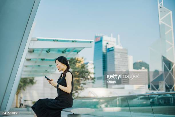 Young woman using smartphone on urban balcony, with highrise corporate buildings behind as background