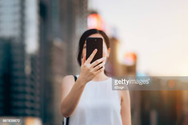 young woman using smartphone outdoors in front of blurry city scene - obscured face stock pictures, royalty-free photos & images