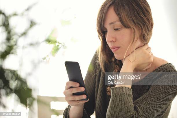 young woman using smartphone - cris cantón photography stock pictures, royalty-free photos & images