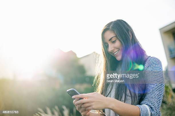 young woman using smartphone - sean malyon stock pictures, royalty-free photos & images