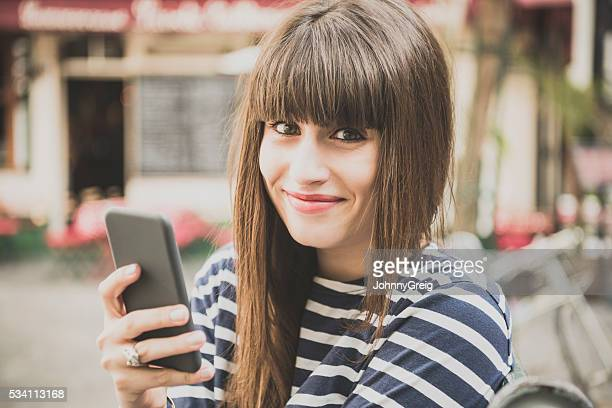 Young woman using smartphone smiling
