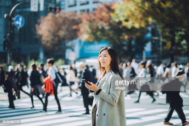 young woman using smartphone to look for direction in city street in tokyo - karte navigationsinstrument stock-fotos und bilder