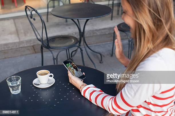 young woman using smartphone to video chat in cafe - long distance relationship stock pictures, royalty-free photos & images