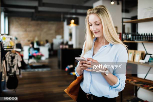 young woman using smartphone while clothes shopping - kunde stock-fotos und bilder