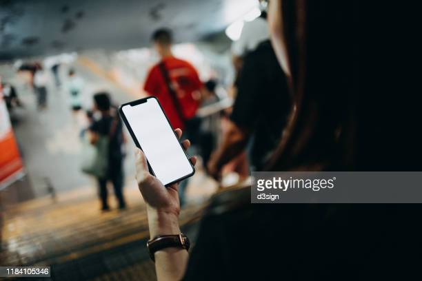 young woman using smartphone while commuting in the city as she walks pass a pedestrian tunnel - 肩越し ストックフォトと画像