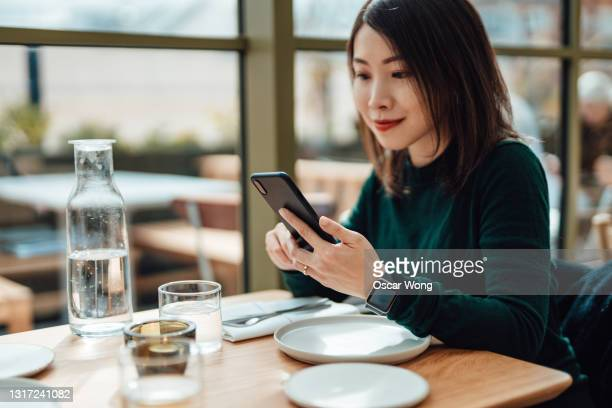 young woman using smartphone while sitting at restaurant - table stock pictures, royalty-free photos & images