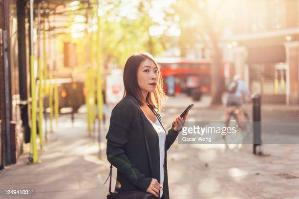 young woman using smartphone while waiting for transport in the city - finding stock pictures, royalty-free photos & images