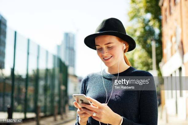 young woman using smartphone with headphones, smiling - all shirts stock pictures, royalty-free photos & images