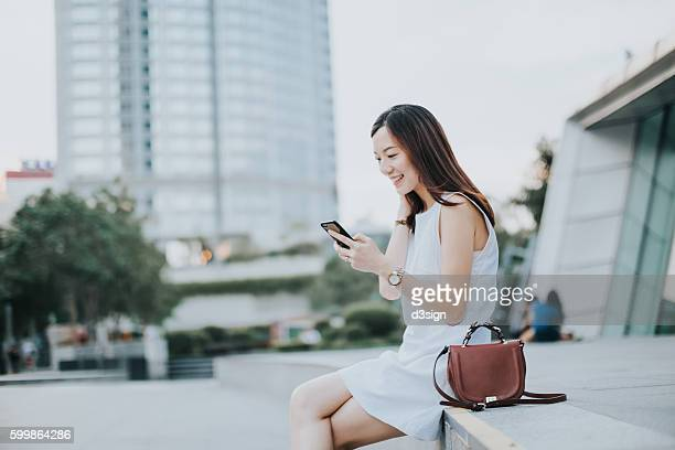 young woman using smartphone with smile in urban park - brown purse stock pictures, royalty-free photos & images