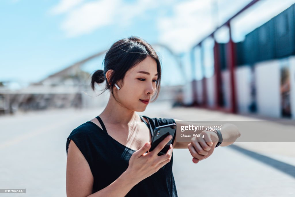 Young woman using smartwatch and doing outdoor workout in the city : Stock Photo