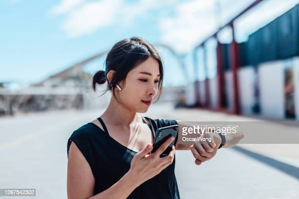 young woman using smartwatch and doing outdoor workout in the city - mobile app stock pictures, royalty-free photos & images