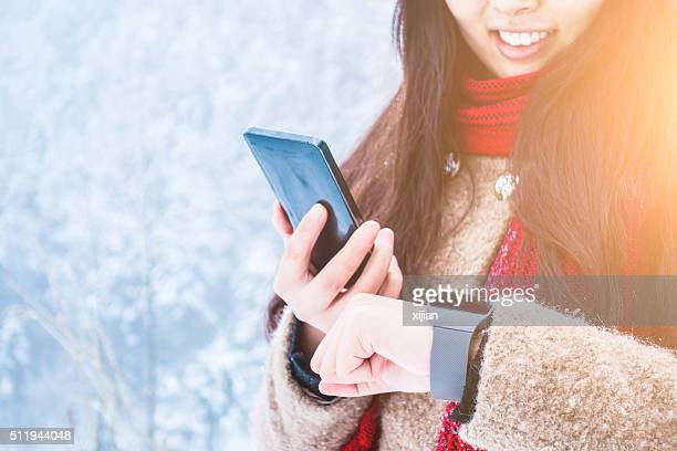 Young woman using smartwatch and smartphone