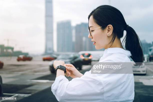 young woman using smartwatch while walking to her car in outdoor car park in city - elektronische organiser stockfoto's en -beelden