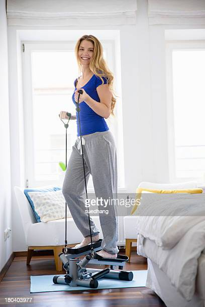 Young woman using step machine at home
